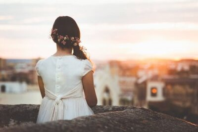Poster girl in communion dress looking at city on sunset