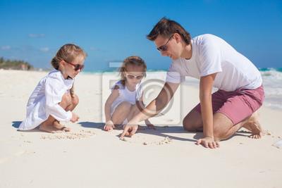 Glücklicher Vater und seine entzückende kleine Töchter spielen auf der
