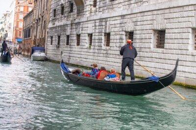 Gondoliers helping tourists exploring city, Venice