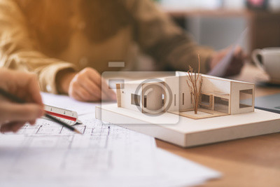 Poster Group of an architect working and discussing about an architecture model together with shop drawing paper on table in office