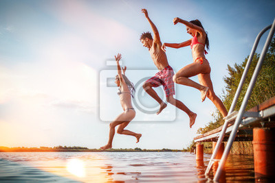 Poster Group of friends jumping into the lake from wooden pier.Having fun on summer day.