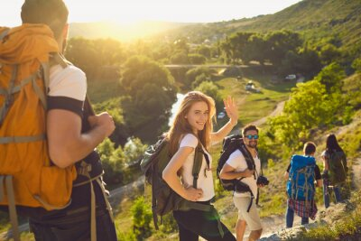 Poster Group of happy backpackers trekking on sunny day. Young tourists traveling and enjoying active summer vacation. Smiling woman looking at camera and waving hand walking down hiking trail with friends