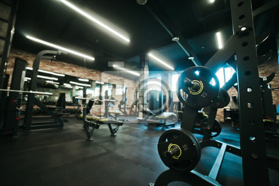 Poster Gym equipment. Dark Gym with barbells on rack. Fitness workout center. Sport concept.
