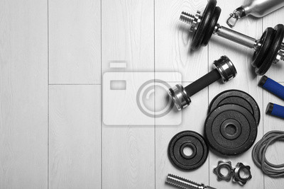 Poster Gym equipment on wooden floor, flat lay. Space for text