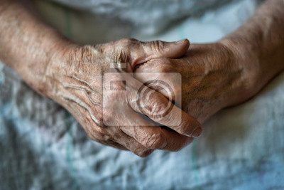 Poster Hands of an old woman folded one over the other. Elderly woman with folded hands. Hands of an old woman close up.