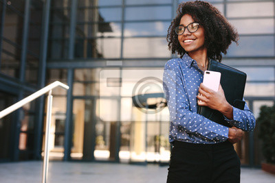 Poster Happy business woman standing outside a office building