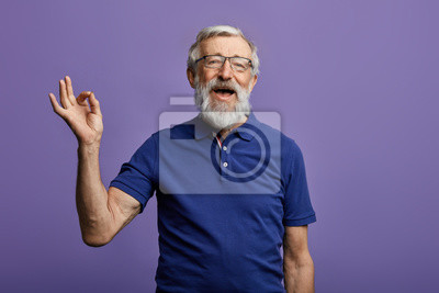 Poster happy positive handsome old man shows Ok sign, no problems, health is ok.everything is ok. close up portrait. isolated blue background. happiness, success concept