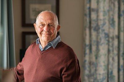 Poster Happy senior man looking at camera at home