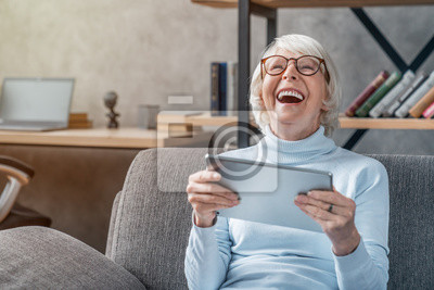 Poster Happy senior woman looking and laughing at her digital tablet on sofa