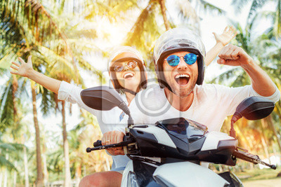 Poster Happy smiling couple travelers riding motorbike scooter in safety helmets during tropical vacation under palm trees