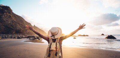 Poster Happy woman with arms up enjoy freedom at the beach at sunset. Wellness, success, freedom and travel concept