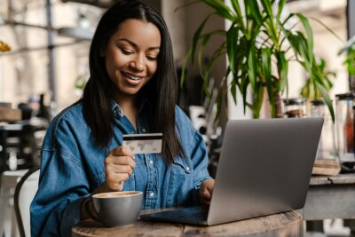 Poster Happy young african woman holding credit card
