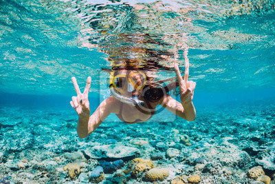Poster Happy young woman swimming underwater in the tropical ocean