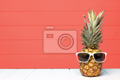 Poster Hipster pineapple with sunglasses against a living coral colored wood background. Minimal summer concept.