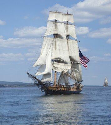 Poster Hohe Lieferung mit der amerikanischen Flagge Segeln auf blauem Wasser