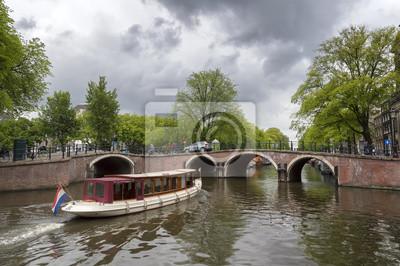 Holländisches Boot, das eine Brücke im sieben Brückenbereich an einem regnerischen Tag in Amsterdam nähert