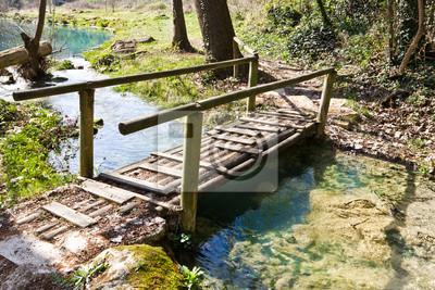 Holzbrücke auf dem Weg neben dem Fluss Elsa, Toskana, Italien.