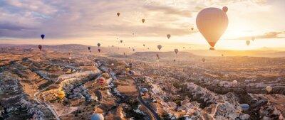 Poster Hot air balloons flying above Göreme, Cappadocia (Kapadokya) Anatolia, Turkey at sunrise. Panoramic view of villages and fairy chimneys. Popular touristic destination for summer vacation holidays