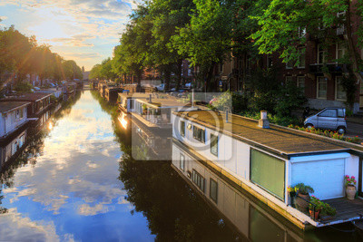 Houseboats at the UNESCO world heritage canals of Amsterdam, The Netherlands, on a sunny summer morning with a blue sky and clouds and a mirror reflection