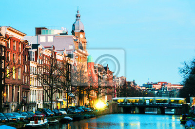 Illuminated bridge and historical buildings in Amsterdam, Netherlands at night