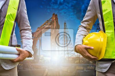 Poster Ingenieur hält Bauzeichnung und Sicherheit Offizier hält harten Hut mit Baumaschinen in der Nacht im Hintergrund.