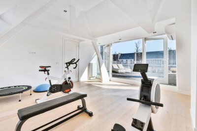 Poster Interior of light house room furnished with gym equipment of bench and cycling machine