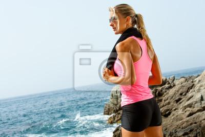 Junge Fitness Frau an der Küste mit Handtuch.