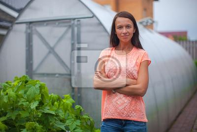 Junge Frau in der Nähe ihres Gewächshaus
