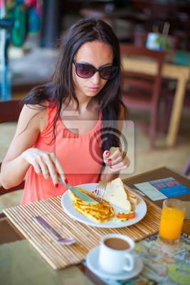 Junge Frau mit Frühstück im Resort Restaurant im Freien
