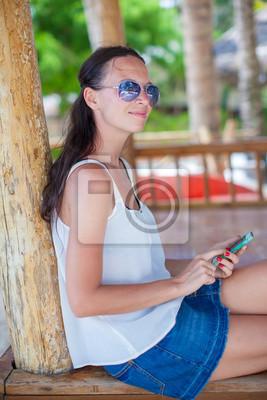 Junge Frau sitzt auf der Brücke und schaut auf ihr Handy