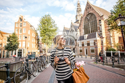 Poster Junge Frau Touristen stehen mit Foto-Kamera auf der Brücke in der Nähe der alten Kirche am Morgen in der Altstadt von Amsterdam Stadt