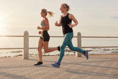 Poster Junge Frauen, die entlang einer Strandpromenade laufen