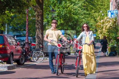 Junge glücklich kaukasisch Paar auf Fahrrädern in alten Straßen in Amsterdam