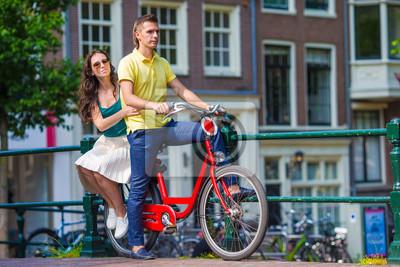 Junge glückliche kaukasische Paare auf Fahrrädern in alten Straßen in