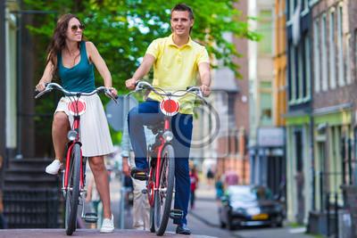 Junge glückliche kaukasische Paare auf Fahrrädern in Amsterdam