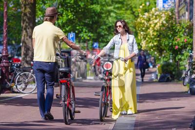 Junge glückliche Paare auf Fahrrädern in alten Straßen in Amsterdam