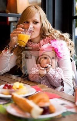 Junge Mutter und Tochter mit einem gemeinsamen Frühstück in einem Pa