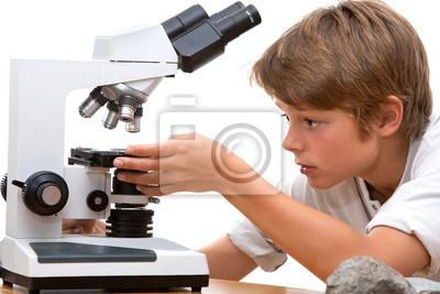 Junge Schüler arbeiten mit Mikroskop.