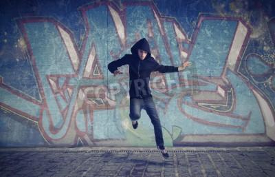 Poster Junger Mann springt mit Graffiti in den Hintergrund