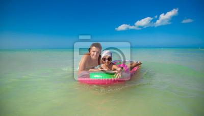 Junger Vater mit kleinen Tochter auf einer Luftmatratze im Meer