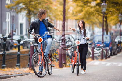 Junges glückliches kaukasisches Paar auf Fahrrädern in den alten Straßen in Amsterdam
