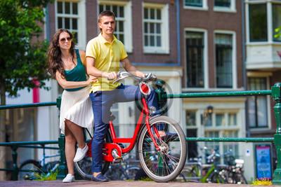 Junges Paar glücklich mit dem Fahrrad auf Brücke in Amsterdam