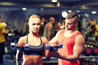 Poster Junges Paar mit Hanteln Muskeln in der Turnhalle