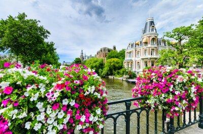 Kanal in Amsterdam mit Blumen auf einer Brücke