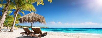 Poster Karibischer Palm Beach mit Holzstühlen und Stroh-Regenschirm - idyllische Insel