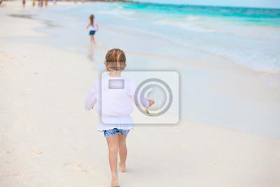 Kleines Mädchen auf weißen Sandstrand läuft in Mexiko
