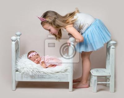 Kleines mädchen sitzt neben ihrer neugeborenen schwester wandposter