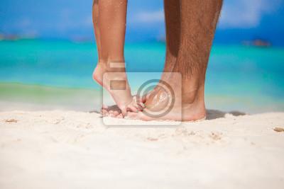 kleines Mädchen steht auf Füßen ihres Vaters am weißen Sandstrand