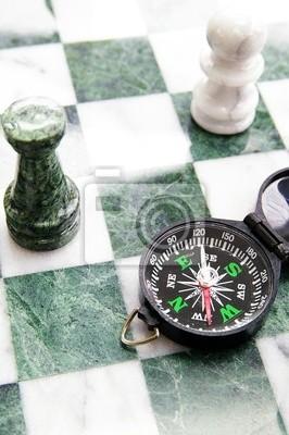 Kompass auf einem Schachbrett und Schachfiguren