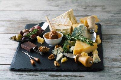 Poster Köstliche Käse auf einem Brett mit Honig, Nüsse auf einem weißen backgro